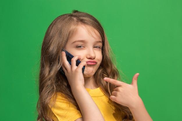 トレンディな緑のスタジオの背景に携帯電話で笑って立って、幸せな十代の少女。