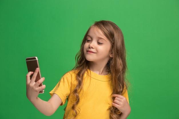 トレンディな緑のスタジオの壁を越えて携帯電話で笑って立っている幸せな十代の少女