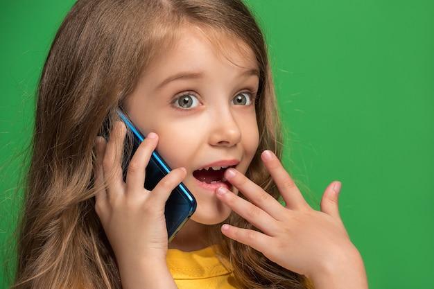 トレンディな緑のスタジオで携帯電話で笑って立っている幸せな十代の少女