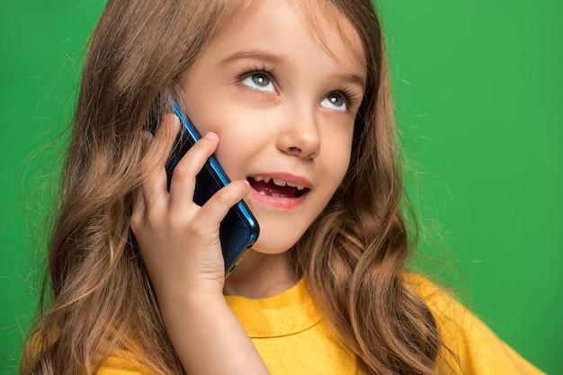 행복 한 십 대 소녀 서, 유행 녹색 스튜디오를 통해 휴대 전화와 함께 웃 고.