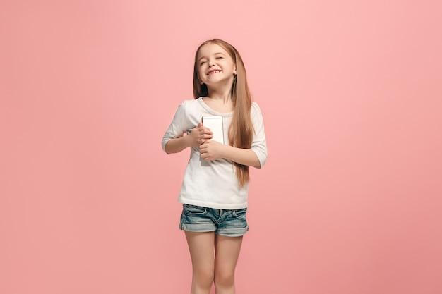 トレンディなピンクの上に携帯電話で笑って立っている幸せな十代の少女。美しい女性の半身像