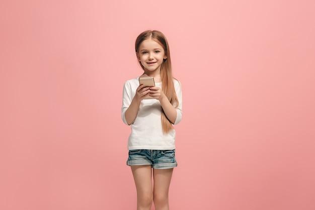 トレンディなピンクのスタジオの背景の上に携帯電話で笑って立って、幸せな十代の少女。美しい女性の半身像。人間の感情、表情の概念。