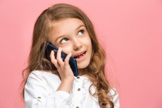 トレンディなピンクのスタジオの背景の上に携帯電話で笑って立って、幸せな十代の少女。美しい女性のハーフレングスの肖像画。人間の感情、顔の表情の概念。