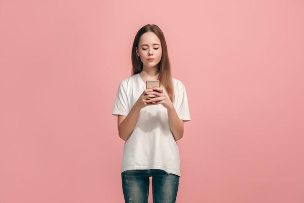 トレンディなピンクのスタジオの背景の上に携帯電話で笑って立って、幸せな十代の少女。美しい女性の半身像