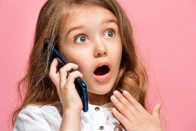 Счастливый подросток девушка стоя, улыбаясь с мобильным телефоном на модном розовом фоне студии.