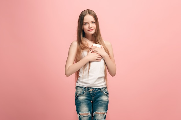 トレンディなピンクのスタジオの背景の上に携帯電話で笑って立っている幸せな十代の少女。