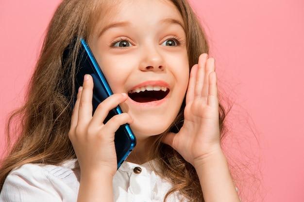 トレンディなピンクのスタジオの壁を越えて携帯電話で笑って立っている幸せな十代の少女