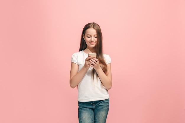 Счастливая девушка-подросток стоит, улыбаясь с мобильным телефоном над модной розовой стеной студии
