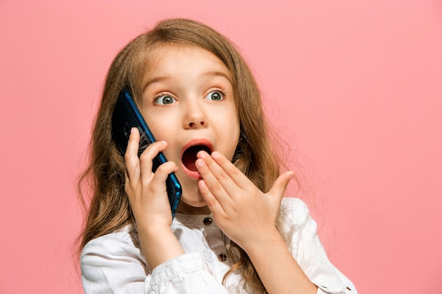 Счастливая девушка-подросток стоя, улыбаясь с мобильным телефоном над модной розовой студией