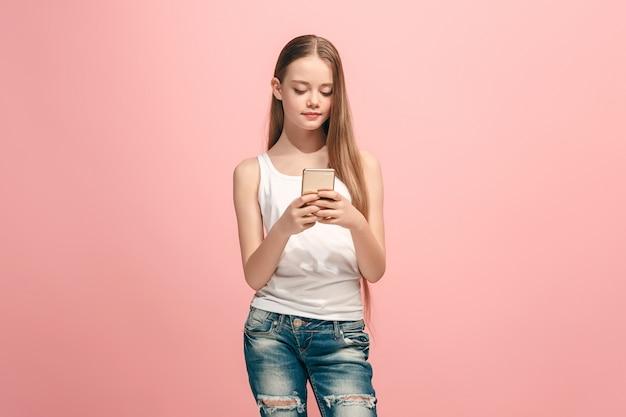 トレンディなピンクのスタジオで携帯電話で笑って立っている幸せな十代の少女
