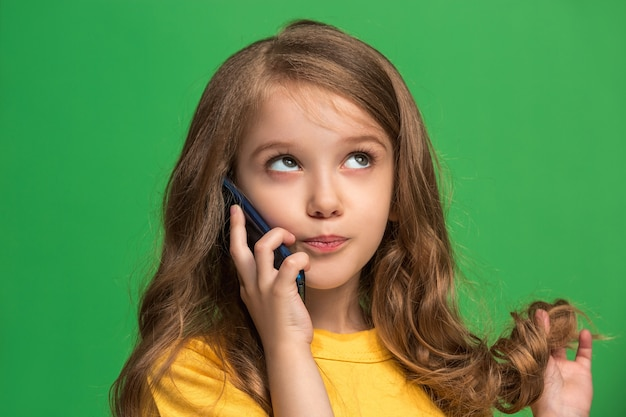 Felice ragazza adolescente in piedi, sorridente con il cellulare sul verde alla moda. bellissimo ritratto femminile a mezzo busto