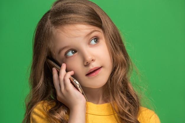 Felice ragazza adolescente in piedi, sorridente con il telefono cellulare su sfondo verde alla moda per studio