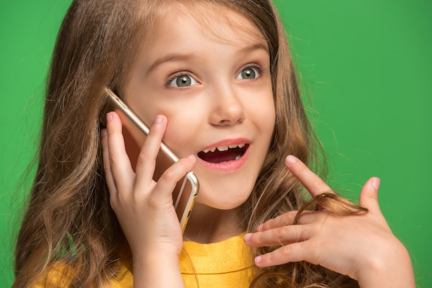 Happy teen girl standing, smiling with mobile phone over trendy green studio