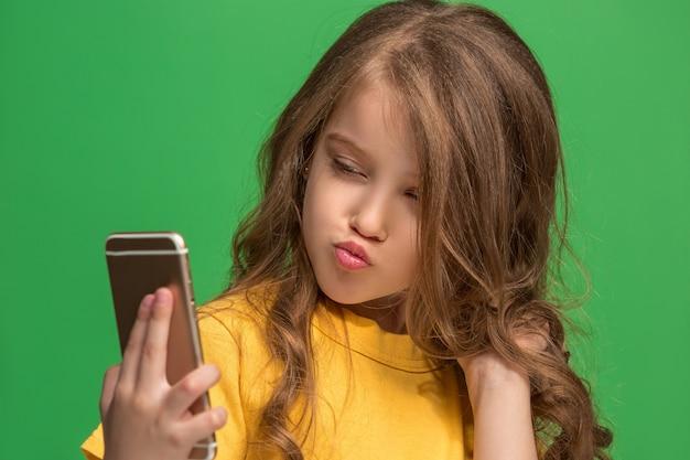 Ragazza teenager felice in piedi, sorridente con il telefono cellulare su studio verde alla moda