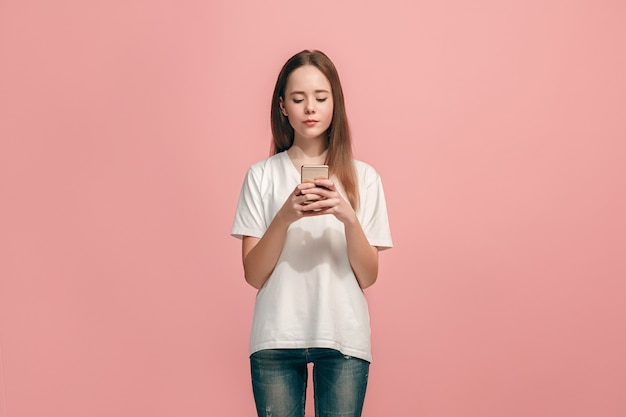Happy teen girl standing, smiling with mobile phone over trendy pink studio background. beautiful female half-length portrait