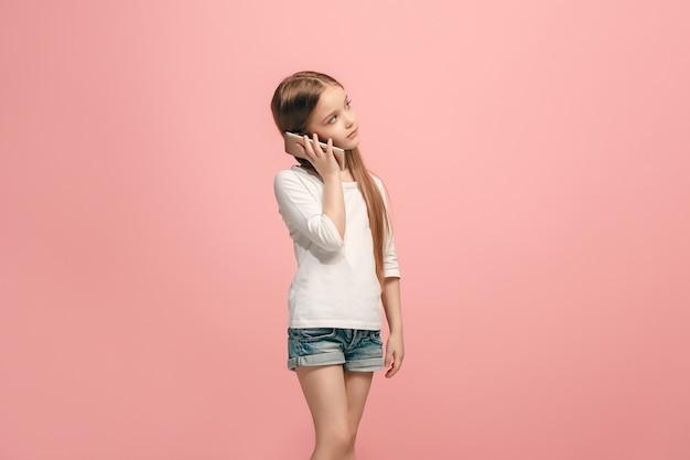 Ragazza adolescente felice in piedi, sorridente con il telefono cellulare su studio rosa alla moda