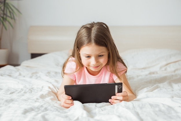 Счастливая девочка-подросток смотрит онлайн-поток фильмов с цифровым мобильным планшетом и лежит на кровати дома утром