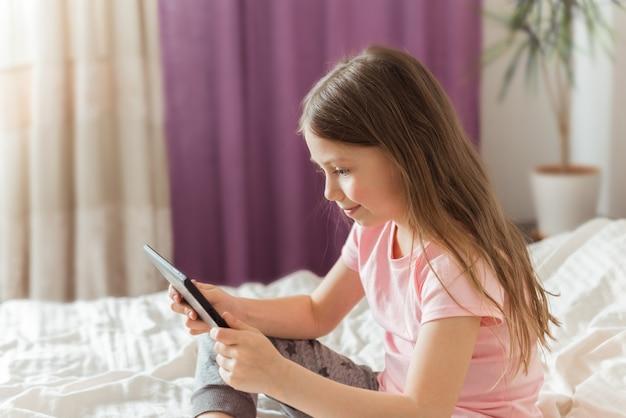 Счастливая девочка-подросток смотрит онлайн-поток фильмов с цифрового планшета