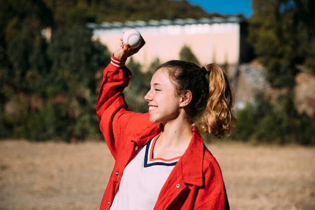 Happy teen girl with ball for baseball