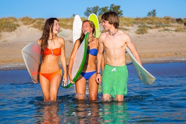 Happy teen surfers talking on beach shore