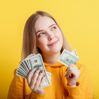 행복 한 10 대 금발 소녀 돈 현금 달러를 손에 들고 신중 하 게 색상 노란색 배경에 고립 된 꿈. 돈 지폐의 세로 젊은 흥분 웃는 여자 스택. 근접 촬영 광장입니다.