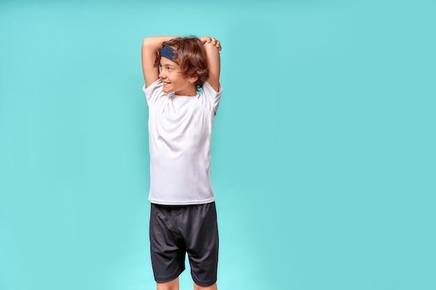 운동복을 입은 행복한 10대 소년은 운동 전에 몸을 스트레칭하면서 멀리 보고 웃고 있습니다.