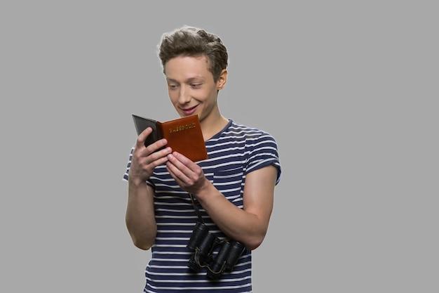 彼のパスポートを見て幸せな10代の少年。灰色の背景にパスポートを持つ若い旅行者の肖像画。旅行のコンセプト。