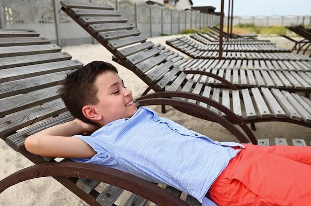 Счастливый подросток, лежа на деревянном шезлонге. красивый ребенок отдыхает на шезлонге во время летних загородных каникул. дети на праздниках