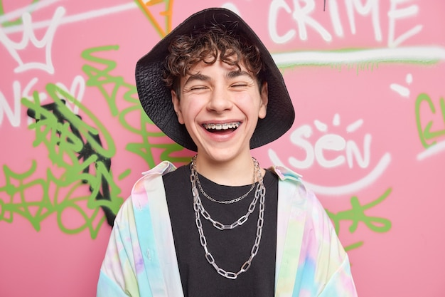 Happy teenage boy with braces on teeth wears stylish clothes with chains around neck has fun with friends poses against colorful graffiti wall as example of modern art