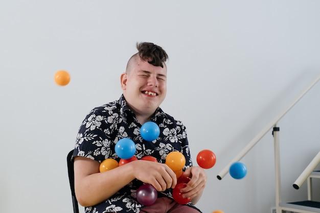 リハビリセンターの白い壁の上の幸せな10代の脳性麻痺の子供