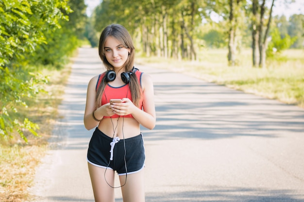 Happy teenage girl in black shorts and red t-shirt holding smartphone and wearing headphones on her shoulders looking at the camera