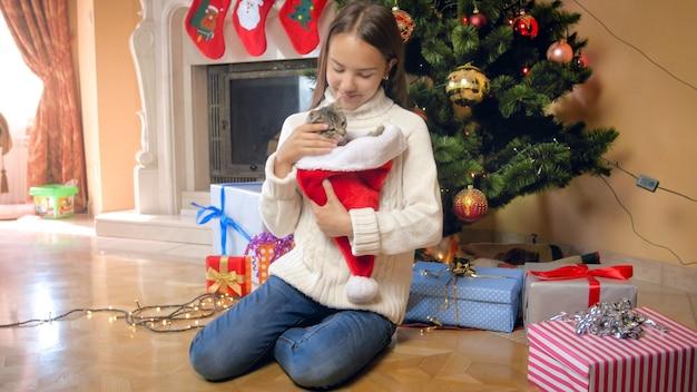 Happy teenage girl caressing her cute kitten under christmas tree