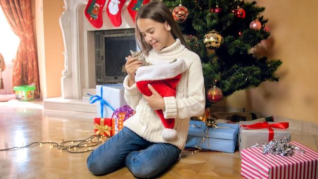 Счастливая девочка-подросток, лаская своего милого котенка под елкой