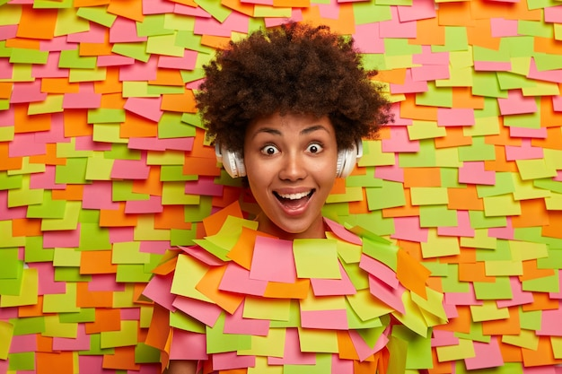 Happy teenage girl has natural curly hair giggles positively listens music in wireless headphones has surprised reaction on stunning news feels upbeat, amused, poses through paper wall adhesive notes