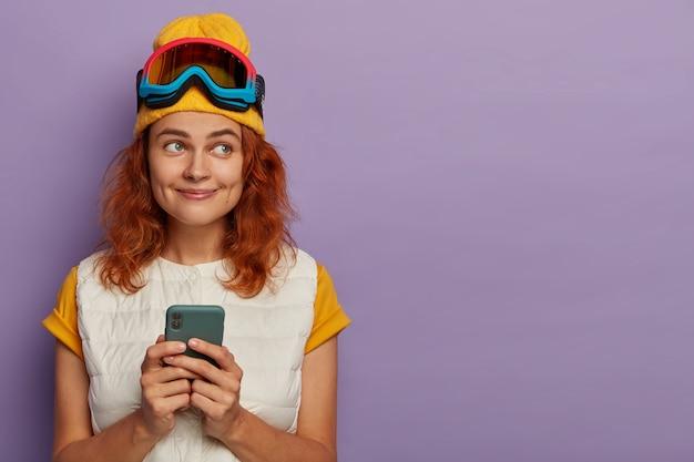 Счастливая девочка-подросток держит современный мобильный телефон, носит маску сноуборда, изолированную на фиолетовой стене.