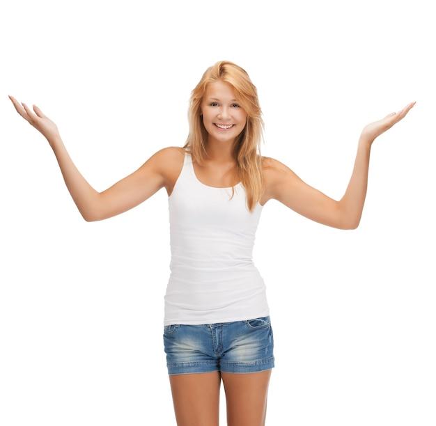 挨拶のジェスチャーを示す空白の白いtシャツで幸せな10代の少女