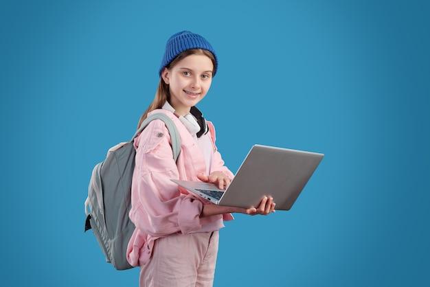 Счастливая девочка-подросток в повседневной одежде держит ноутбук и занимается серфингом в сети, стоя перед камерой на синем фоне