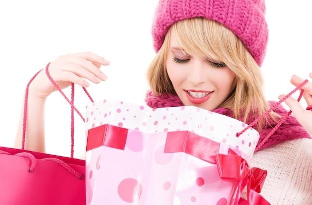 Счастливая девочка-подросток в шляпе с розовыми сумками