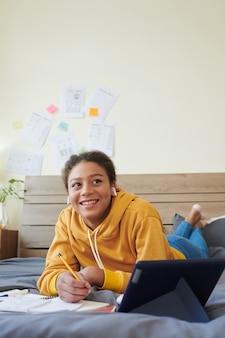 ベッドで横になっている幸せな10代の少女