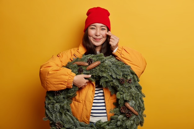 Happy teenage girl makes korean like sign, expreses love and affection, wears red hat and outerwear, holds green handmade wreath, gets ready for christmas