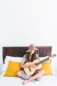 Happy teenage girl playing guitar in bedroom