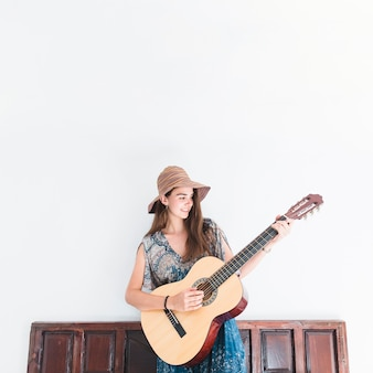 Happy teenage girl playing guitar in front of wall