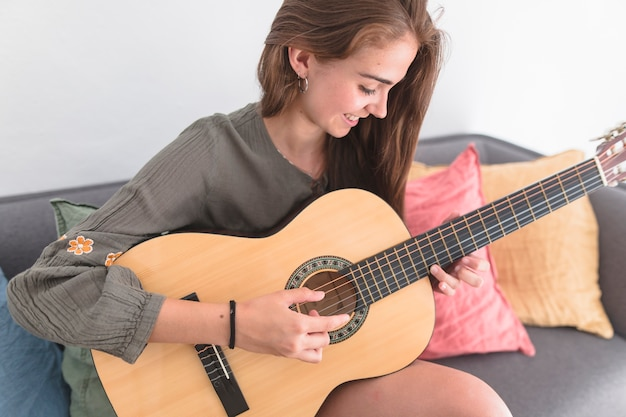 Happy teenage girl playing guitar at home