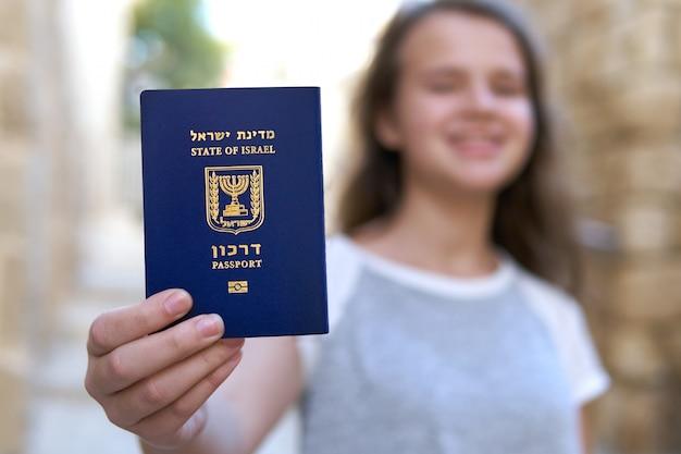 Счастливая девочка-подросток показывает паспорт государства израиль, держа его в руке