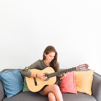 Happy teenage girl sitting on sofa playing guitar against white background
