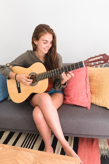 Happy teenage girl sitting on sofa playing guitar at home