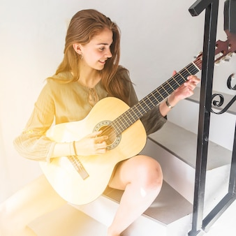 Happy teenage girl sitting on staircase playing guitar