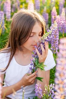 야외 웃 고 행복 한 십 대 소녀입니다. 아름 다운 젊은 십 대 여자 개화 야생 꽃 녹색 배경으로 여름 필드에 휴식. 무료 행복한 아이 십대 소녀, 어린 시절 개념