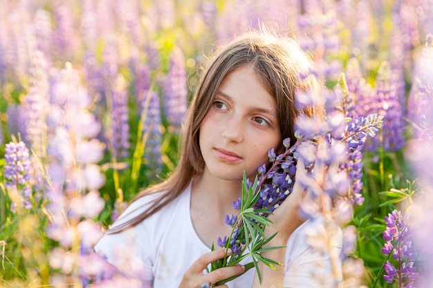야외 웃 고 행복 한 십 대 소녀입니다. 피는 야생 꽃 녹색 배경으로 여름 필드에 쉬고 아름 다운 젊은 십 대 여자