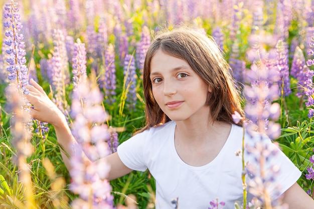 夏のフィールドで休んで屋外で笑顔の幸せな10代の少女